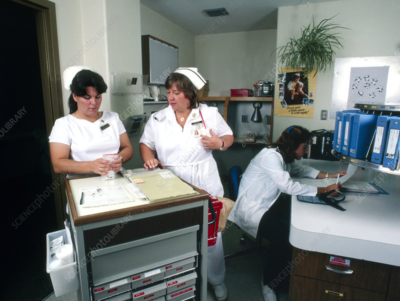 Nurses consulting over a medicine cabinet