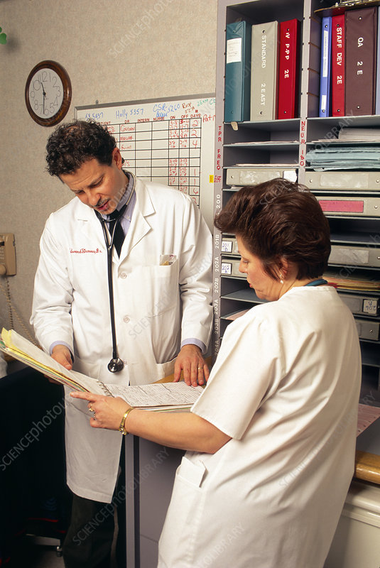 Doctor and nurse consult records at a workstation