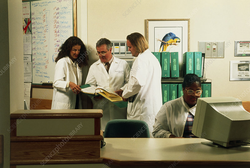Hospital staff with patient records at workstation