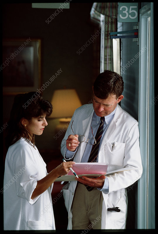 Doctor and nurse discuss records in hospital hall