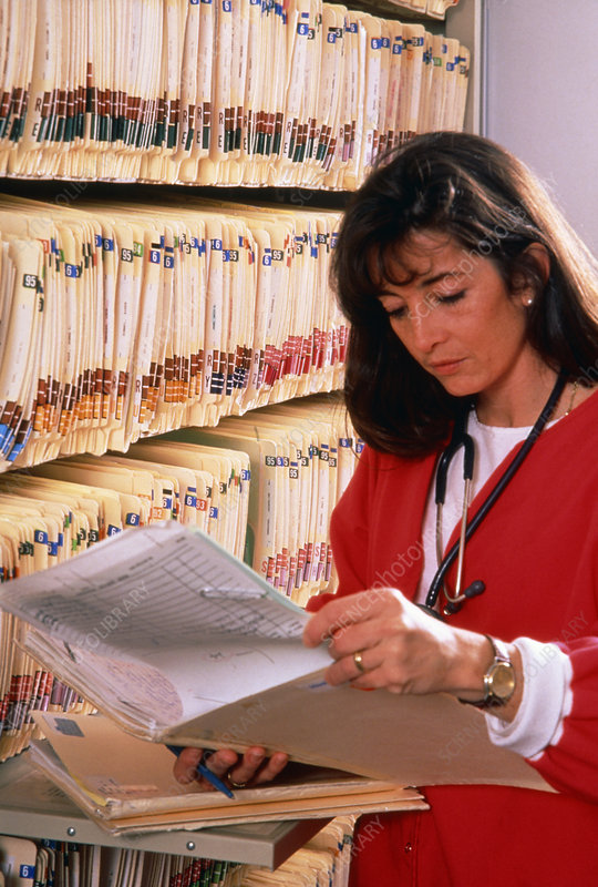 Nurse checks medical records in a filing room