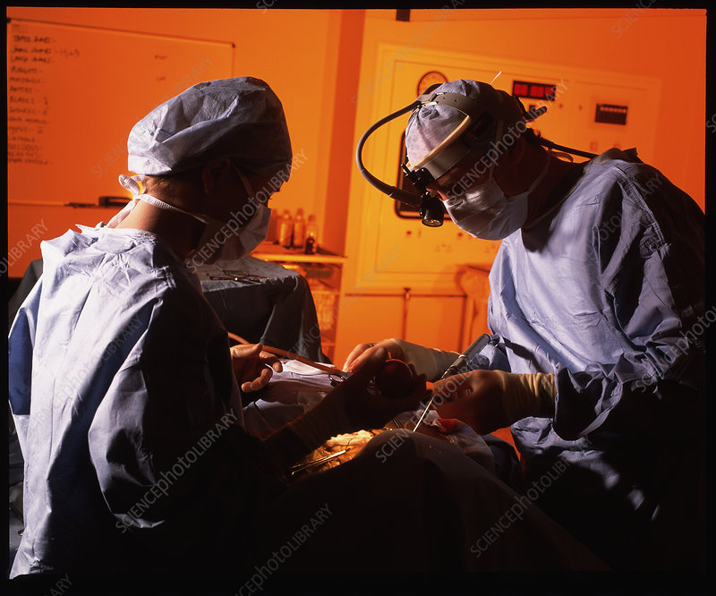 Masked surgeons conduct a surgical operation