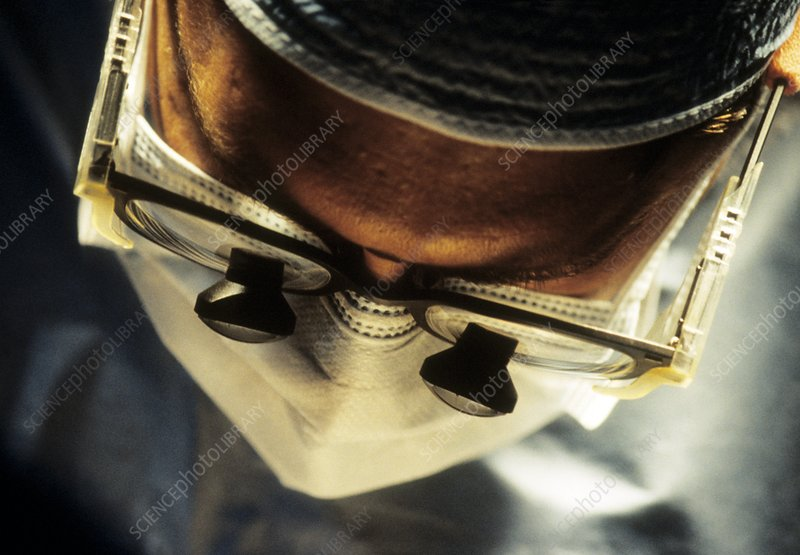 Face of surgeon with magnifying lenses on glasses