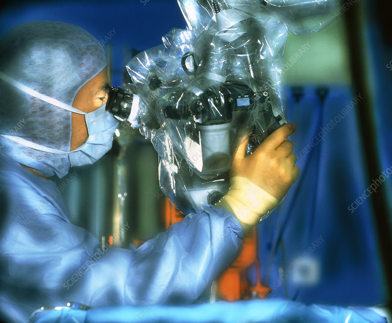 Surgeon using a microscope during microsurgery