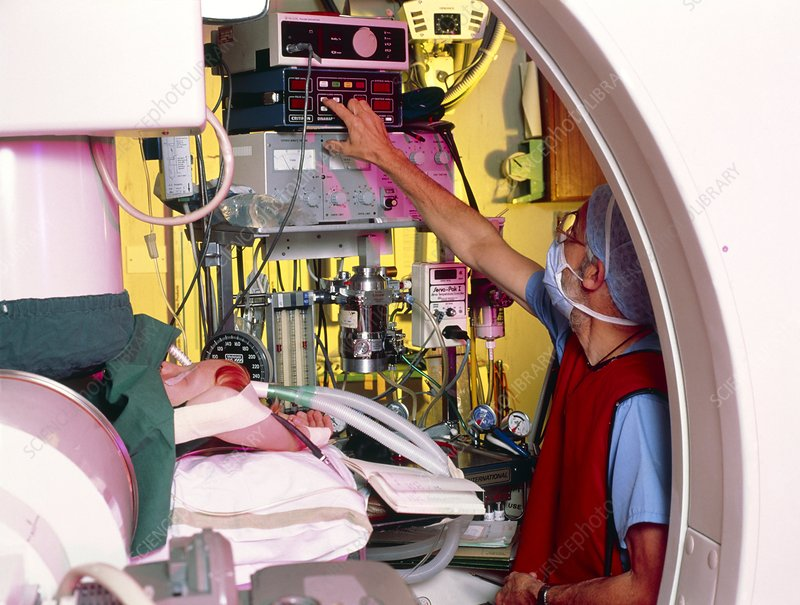 Anaesthetist at work on infant cardiac cath. op.