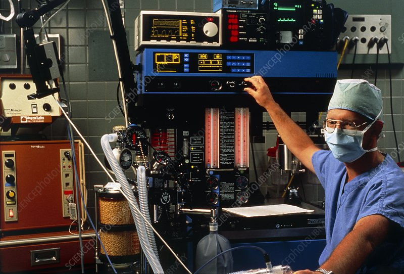 Anaesthetist adjusts anaesthetic equipment