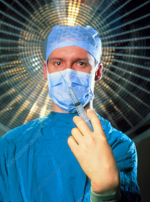 Anaesthetist in surgical dress holds a syringe
