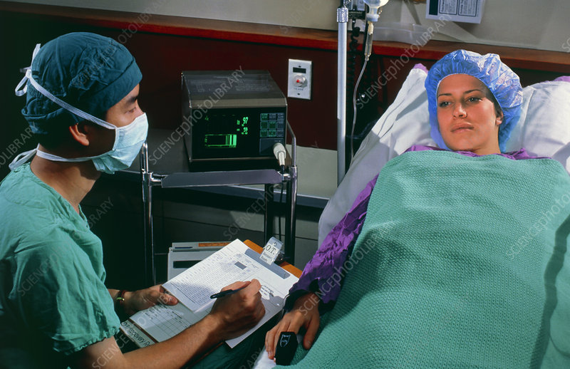 Surgeon monitors female patient after surgery
