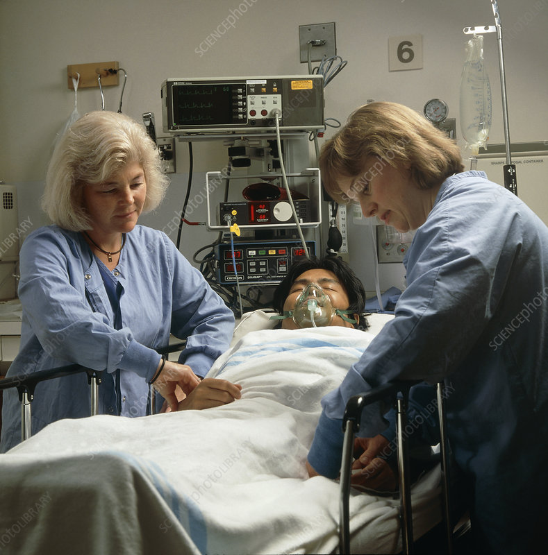 Female nurses monitor a patient after surgery
