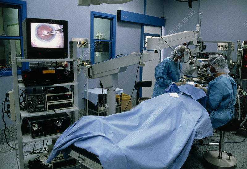Surgeons using microscope to carry out eye surgery