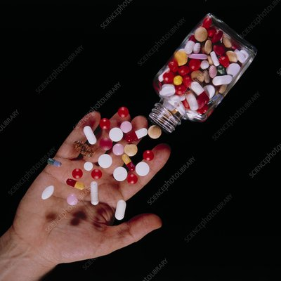 Bottle of assorted pills tipped into a hand