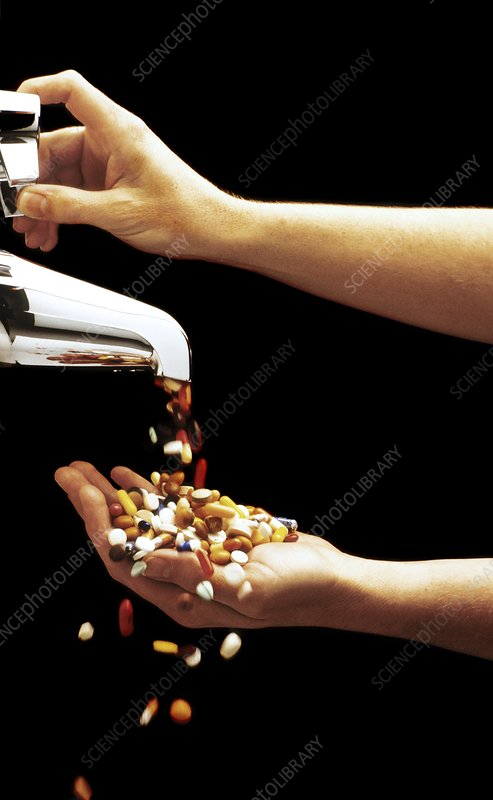 Pills and tablets pouring from a tap into a hand