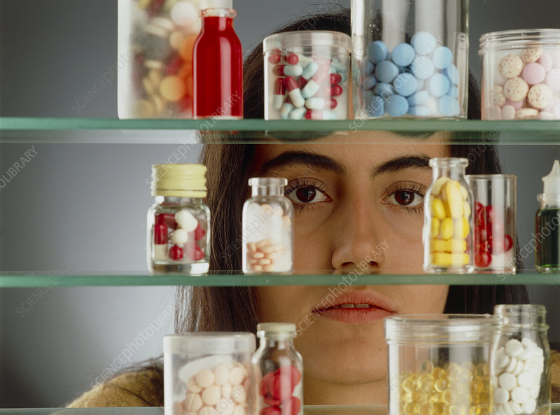 Young woman looks through a medicine cabinet