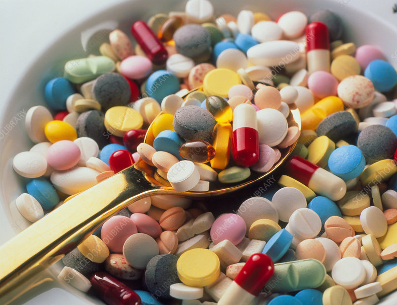 Spoonful of assorted pills, tablets and capsules