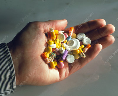 Hand holding assorted pills, tablets & capsules