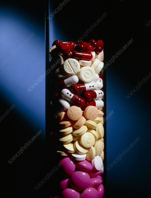 Assorted pills and drug capsules in glass cylinder