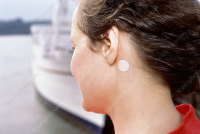 Woman at sea with anti-seasickness patch near ear