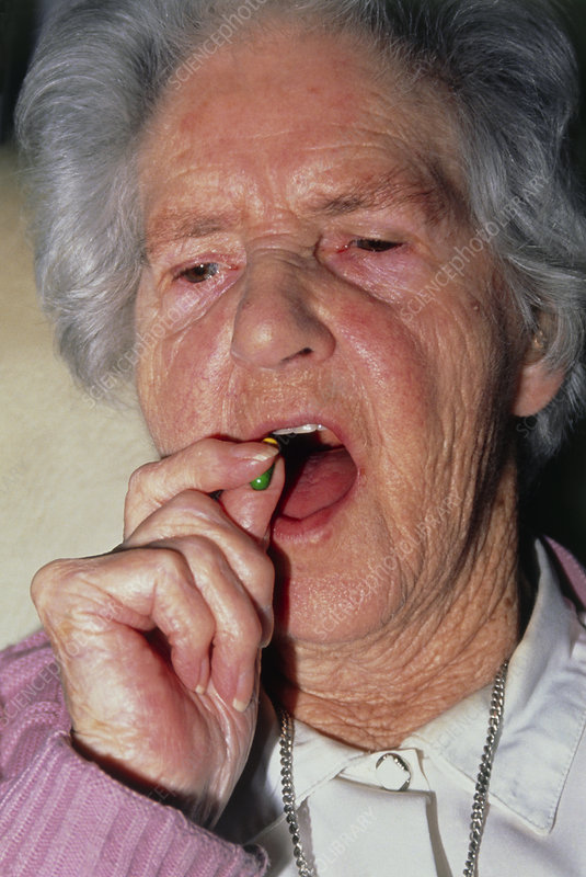 Elderly woman swallows a prescription drug capsule