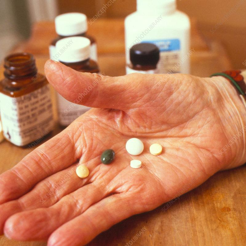 Elderly woman's hand holding drugs