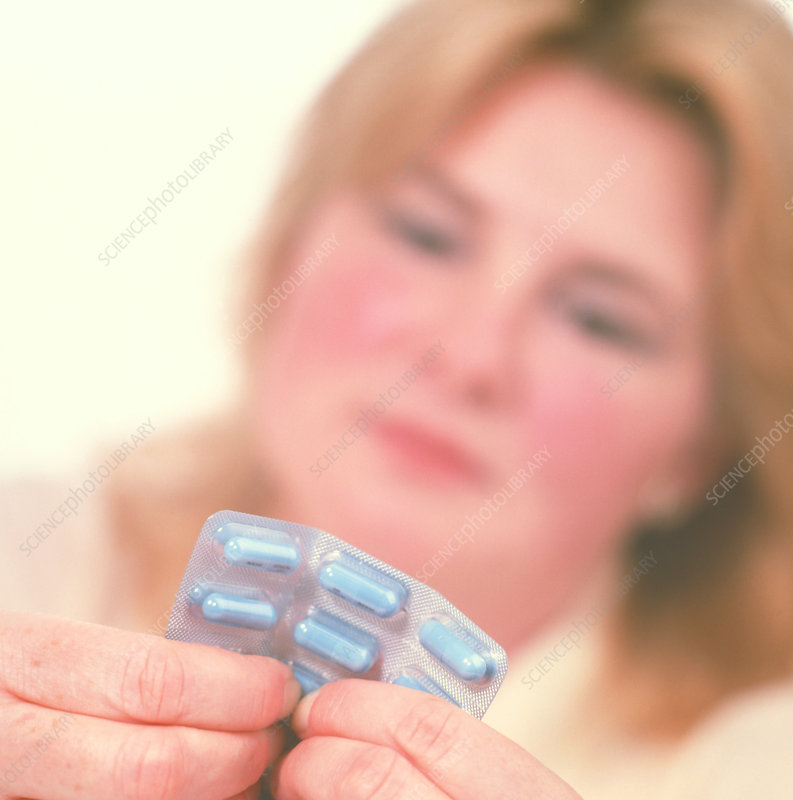 Obese woman holds Xenical weight-loss drug