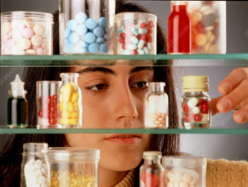 Young woman takes pills from a medicine cabinet