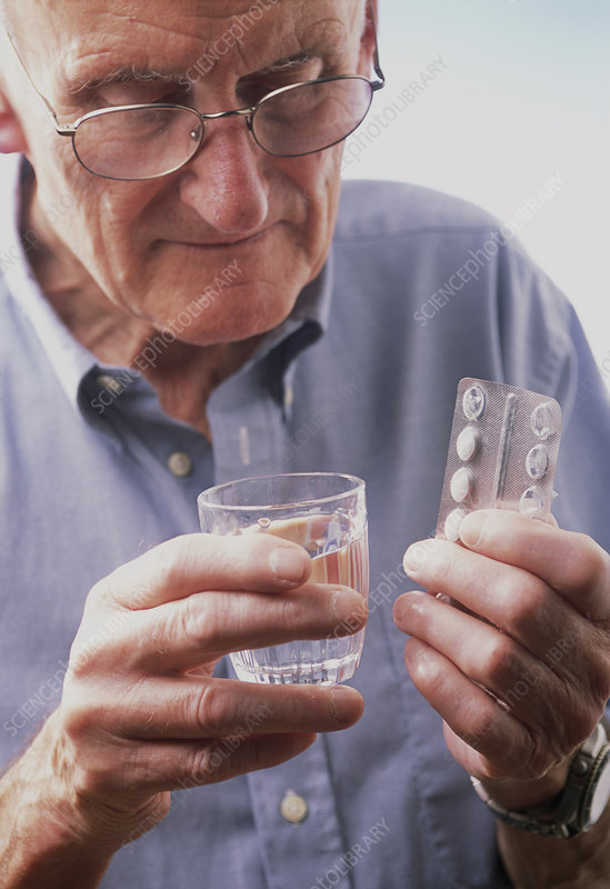 Elderly man taking medication