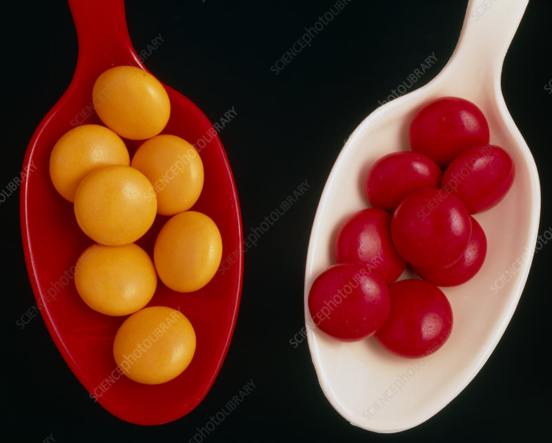 Orange and red multivitamins on plastic spoons