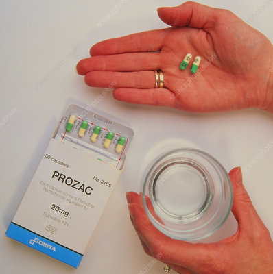 Prozac pack with pills in hand and glass of water