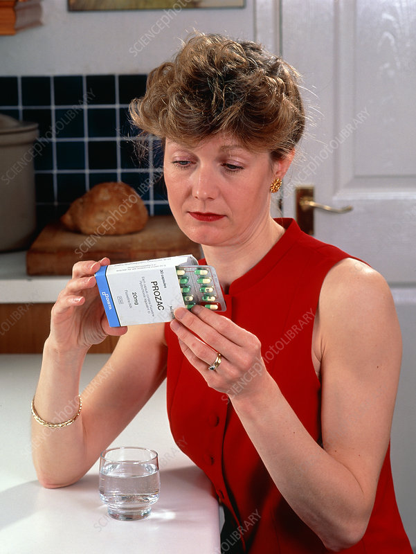 Woman reading dose label on pack of Prozac pills