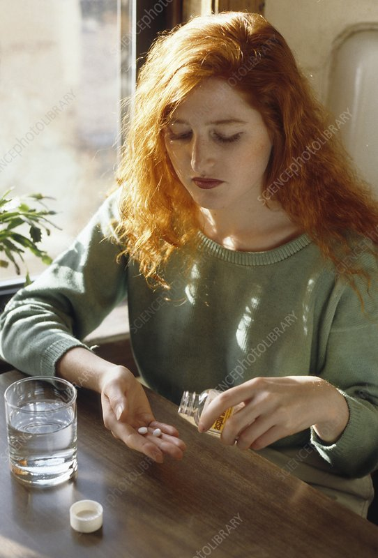 Young woman pouring aspirin pills from a bottle