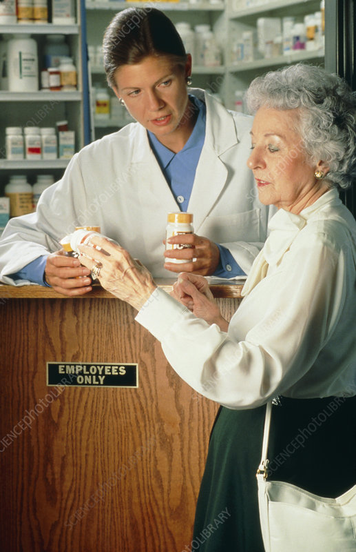 Pharmacist dispensing drugs to customer