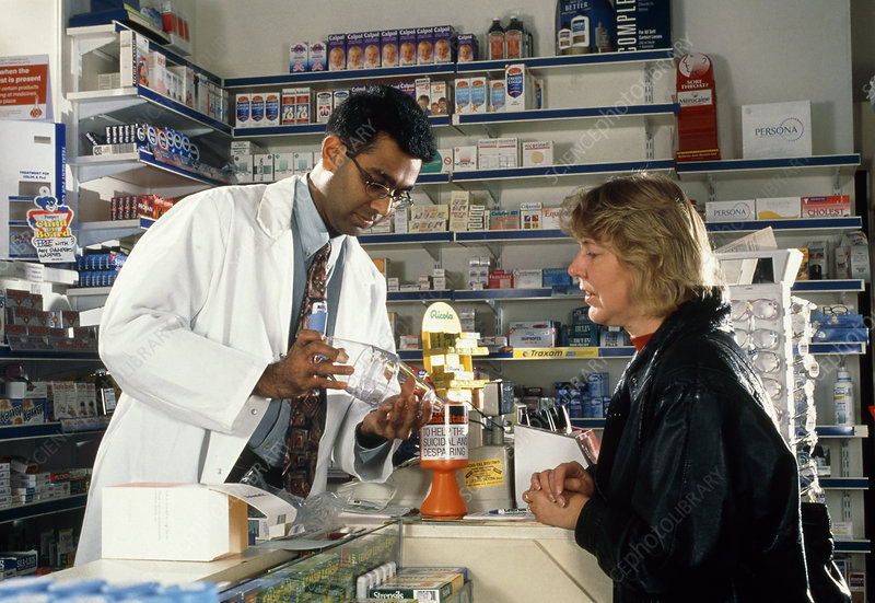 Pharmacist showing a volumatic adaptor to a woman