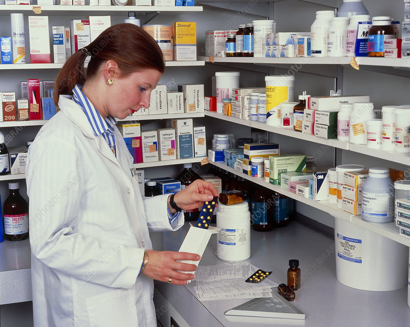 A pharmacist measuring out pills
