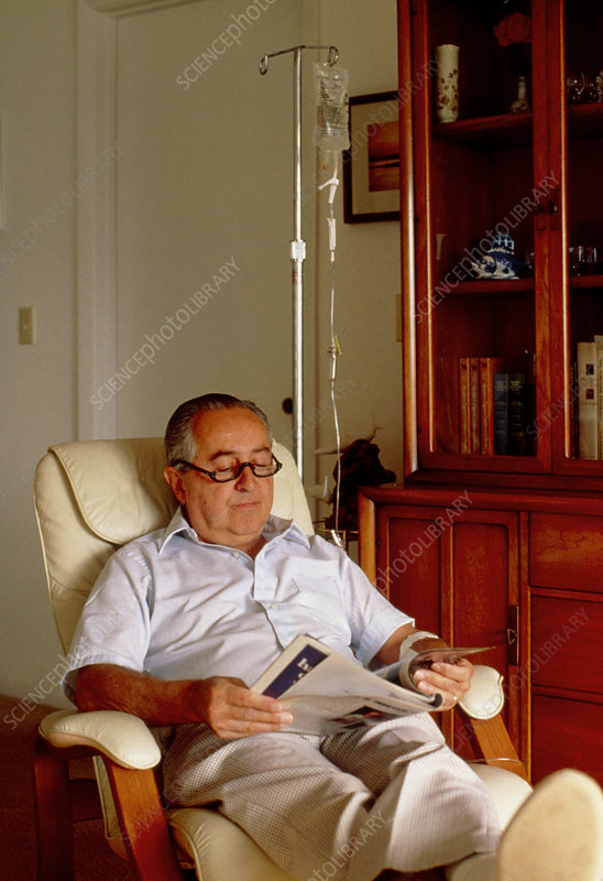 Seated man at home receives an intravenous drip
