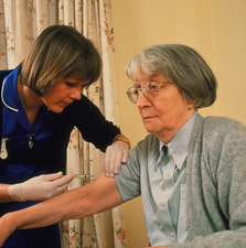 Elderly woman given injection by nurse