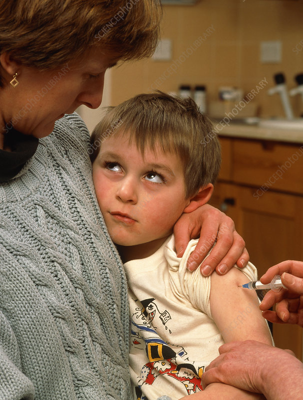 Nurse's hand injecting vaccine into boy's arm