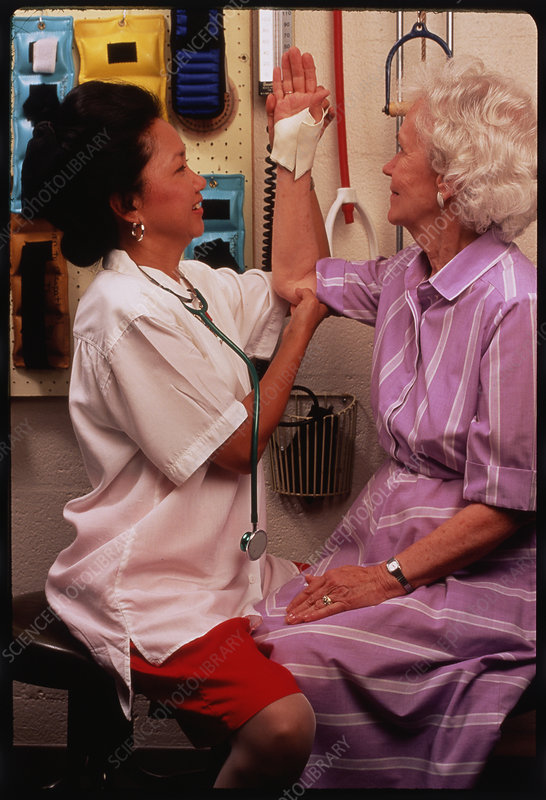 Elderly woman receives physiotherapy