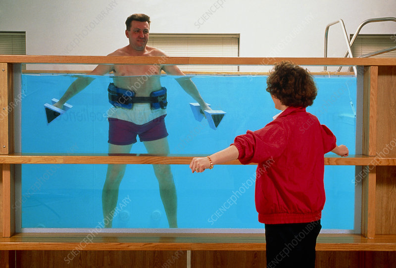 Man exercising with weights in hydrotherapy pool