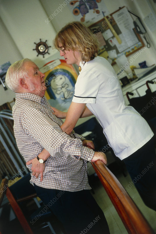 Physiotherapist helping an elderly man stand