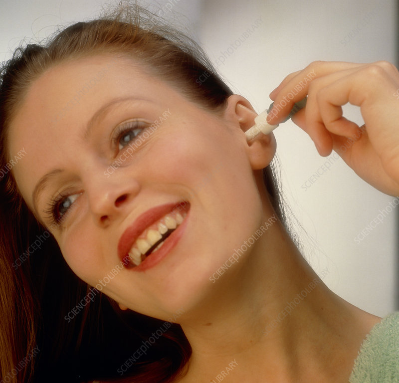 Young woman applying eardrops by herself