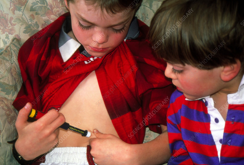 Seven year old boy self-injecting with insulin