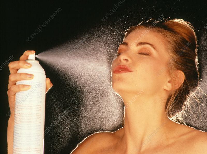 Woman using water spray on face