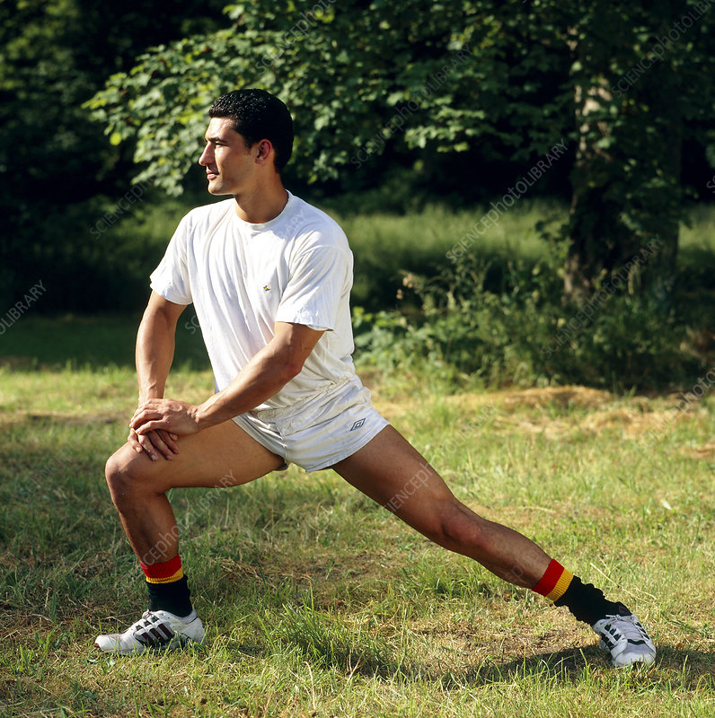 Athletic man doing leg stretch exercise outdoors
