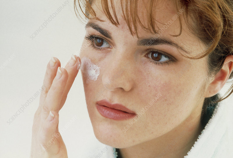 Woman applying facial cream with her finger