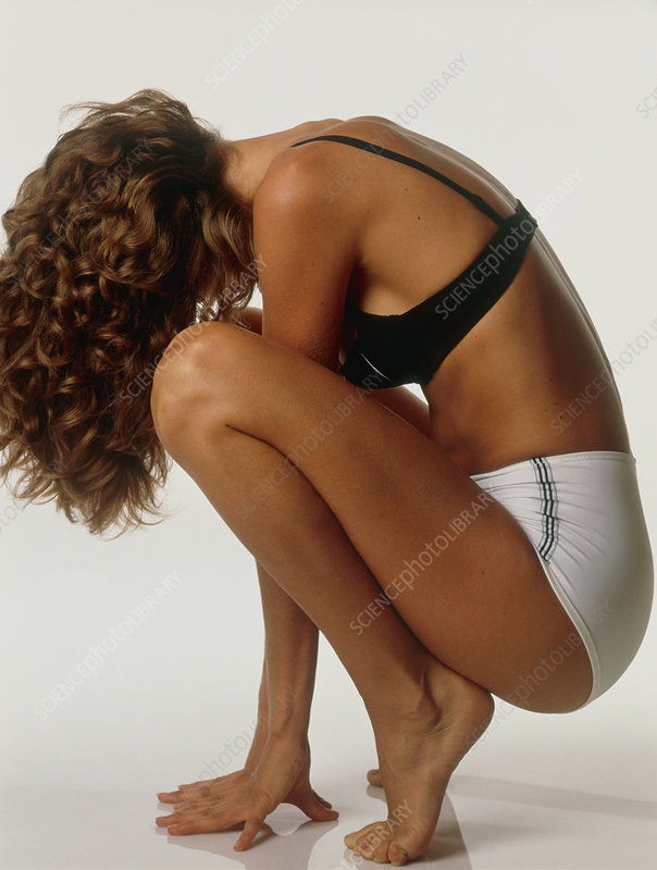 Young woman performs a squatting exercise