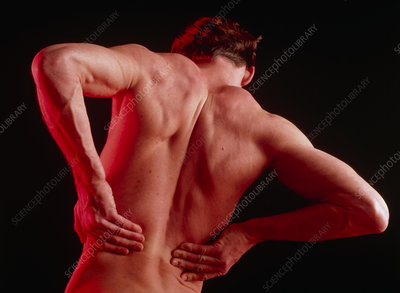 Young man affected by back pain doing self-massage