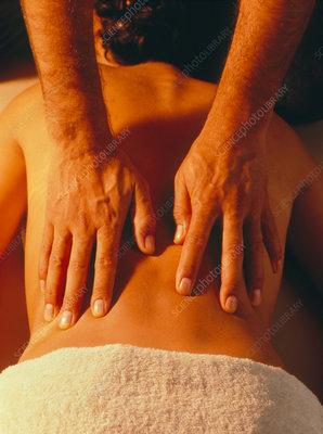 Woman being given a back massage by male masseur