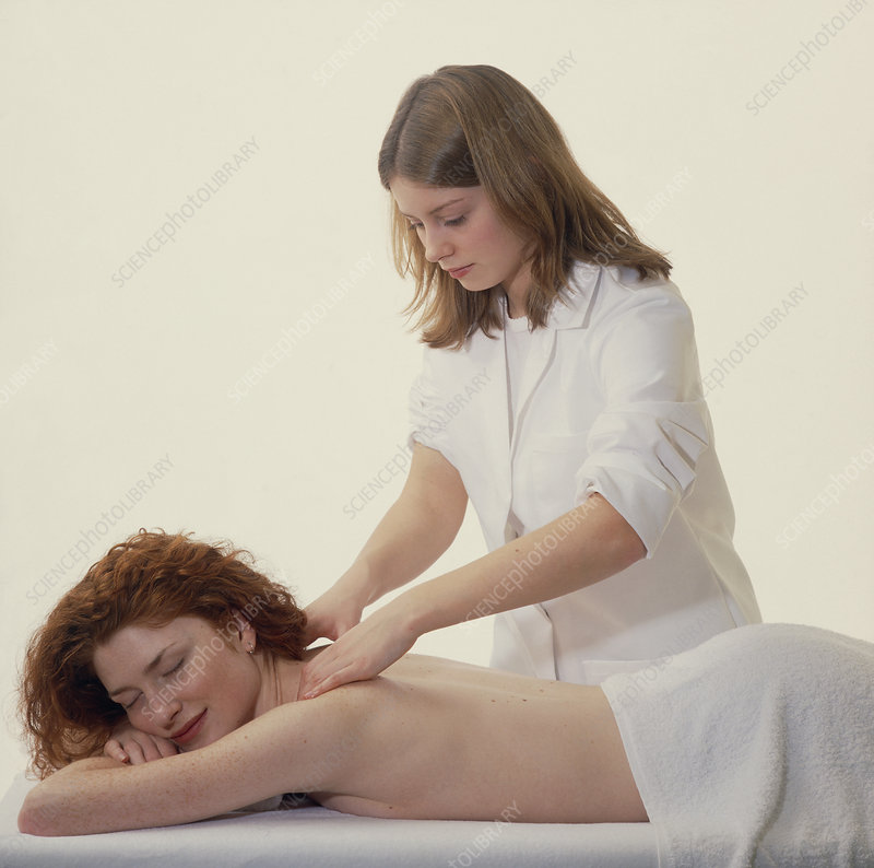 Masseuse massages the neck & shoulders of a woman