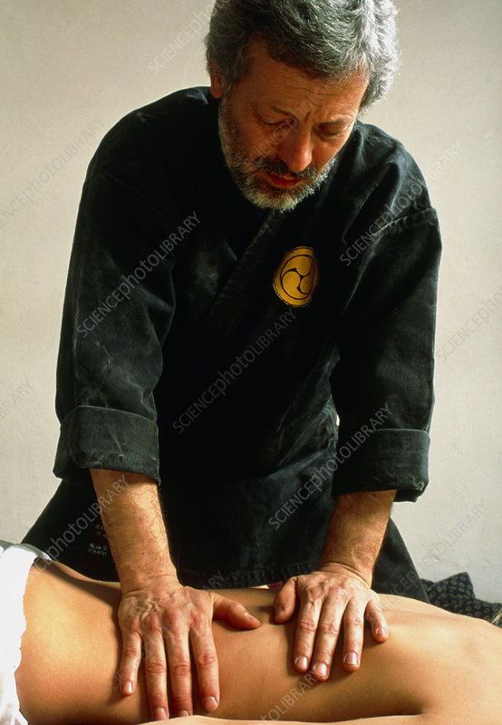 Man carrying out shiatsu massage on a woman's back