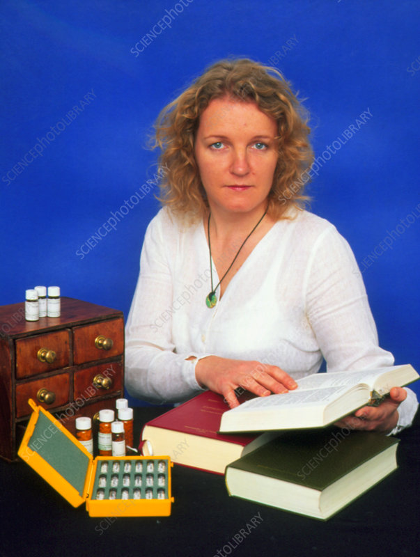 Homeopath with book beside selection of medication